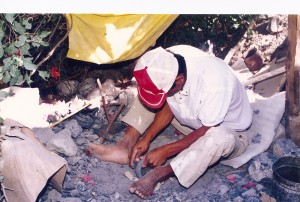 Manuel Olalde working on a toy molcajete